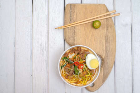 Malay Mee Rebus in the bowl  with chopsticks on white table This dish is made of noodles ,vegetable,egg with a spicy . Archivio Fotografico