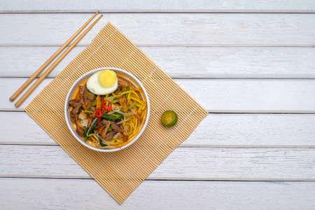 Malay Mee Rebus nella ciotola con le bacchette sul tavolo bianco Questo piatto è fatto di tagliatelle, verdure, uova con un piccante. Archivio Fotografico