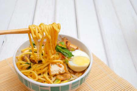 Malay Mee Rebus nella ciotola con le bacchette sul tavolo bianco Questo piatto è fatto di tagliatelle, verdure, uova con un piccante.