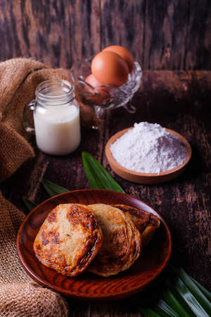 Akok Kedut, egg, coconut, flour , coconut milk and  Pandan leaf on wooden background. Akok Kedut is a traditional dish in Malaysia especially East Coast.