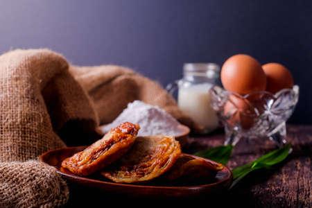 Akok Kedut, egg, coconut, flour , coconut milk and Pandan leaf on wooden background. Akok Kedut is a traditional dish in Malaysia especially East Coast.