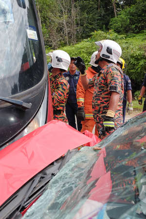 Muadzam Shah, Malaysia - October 18th, 2018 : Firefighter rescuing wounded young man in accident between car, bike and bus  in  Inter Agency Disaster Training Program 2018 at Muadzam Shah. Redakční