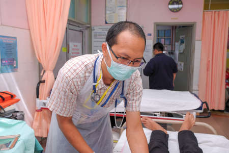 Muadzam Shah, Pahang - October 18th, 2018 : A male doctor who is examining female patients lying on the patients bed during road accidents in  Inter Agency Disaster Training Program