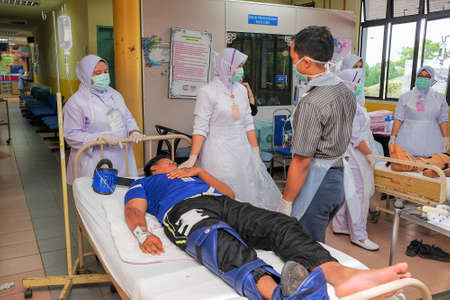 Muadzam Shah, Pahang - October 18th, 2018 : A female doctor who is examining male patients lying on the patient's bed during road accidents in  Inter Agency Disaster Training Program 写真素材 - 120680832