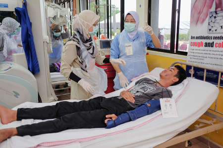 Muadzam Shah, Pahang - October 18th, 2018 : A female doctor who is examining male patients lying on the patient's bed during road accidents in  Inter Agency Disaster Training Program 写真素材 - 120680834
