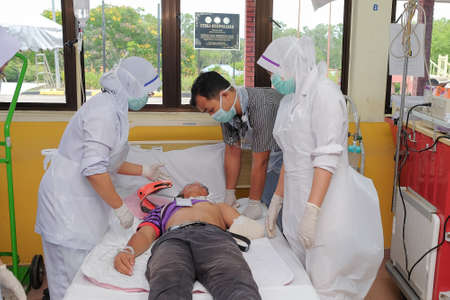 Muadzam Shah, Pahang - October 18th, 2018 : A male doctor who is examining male patients lying on the patient's bed during road accidents in  Inter Agency Disaster Training Program 写真素材 - 120680840