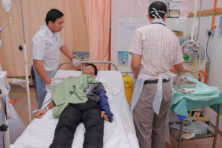 Muadzam Shah, Pahang - October 18th, 2018 : A male doctor who is examining male patients lying on the patient's bed during road accidents in  Inter Agency Disaster Training Program 写真素材 - 120680844