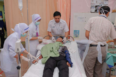 Muadzam Shah, Pahang - October 18th, 2018 : A male doctor who is examining male patients lying on the patient's bed during road accidents in  Inter Agency Disaster Training Program 写真素材 - 120680845