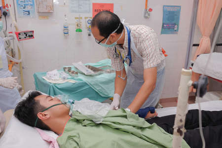 Muadzam Shah, Pahang - October 18th, 2018 : A male doctor who is examining male patients lying on the patient's bed during road accidents in  Inter Agency Disaster Training Program 写真素材 - 120680847