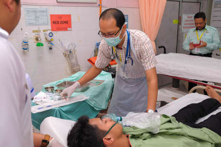 Muadzam Shah, Pahang - October 18th, 2018 : A male doctor who is examining male patients lying on the patient's bed during road accidents in  Inter Agency Disaster Training Program 写真素材 - 120680849