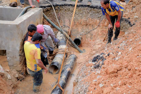 Muadzam Shah, Malaysia - November 1st, 2018  : Construction workers installing new pipe at the construction site Redakční