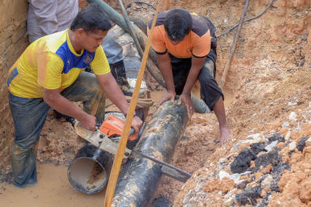 Muadzam Shah, Malaysia - November 1st, 2018  : Worker using chainsaw to cut water pipe in new construction site.