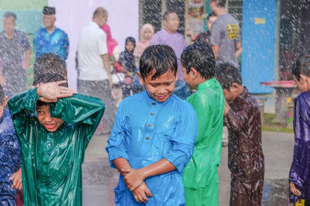 Muadzam Shah, Malaysia -  November 24th  , 2018 : Childrens wearing traditional malay costume are happy to play the water during the flush event of the circumcision participants.