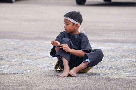 Muadzam Shah, Maleisië - 24 november 2018 - Een Maleisische student met het traditionele Maleisische krijgerskostuum die stappen van Silat uitvoert tijdens een massale besnijdenisceremonie in de tuin van de school. Redactioneel