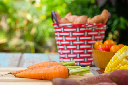 Cherry tomatoes, sweet potato, corn and baby carrot on wooden background