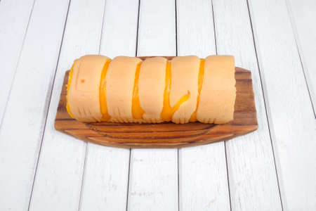 Roll cake  butter cream filling on wooden plate over wooden background Stock Photo