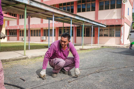 Muadzam Shah, Malaysia - January 3rd, 2019 : The worker clears the clogged sewer drain using drain clog remover  to remove the dirt attached to the channel Éditoriale