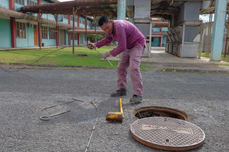 Muadzam Shah, Malaysia - January 3rd, 2019 : The worker clears the clogged sewer drain using drain clog remover Éditoriale