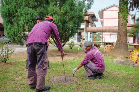 Muadzam Shah, Malasia - 3 de enero de 2019: Los trabajadores mueven la tapa de la alcantarilla para limpiar la línea de alcantarillado en busca de obstrucciones