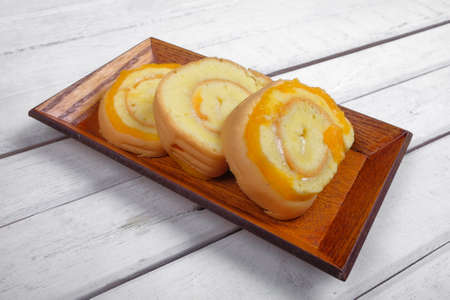 Roll cake  butter cream filling on wooden plate over wooden background 免版税图像