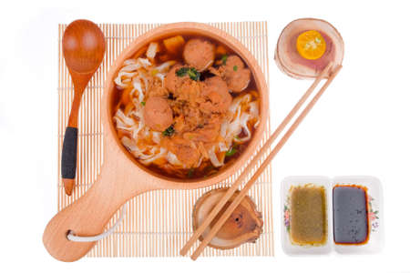 Delicious homemade Bakso, famous traditional Indonesian street food, meatballs with noodles served with chili saucel and soy sauce isolated on white background