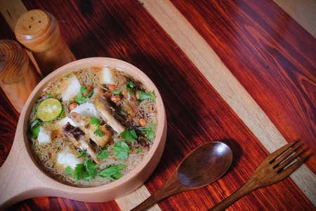 Soto Ayam is a chicken soup served in wooden pan with vegetables and rice