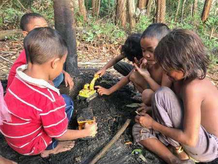 Muadzam Shah, Malaysia - February 19th, 2019 : A goup of aboriginal children playing under the tree at Muadzam Shah, Malaysia