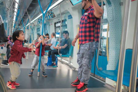 KUALA LUMPUR, MALAYSIA - December 31st ,  2017: Asian Malay little boys playing pole inside a MRT transit in Kuala Lumpur City, Malaysia. Banque d'images - 120681370
