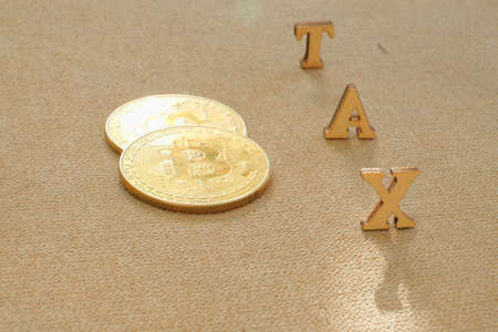 Bitcoin  and next to wooden with TAX letters. Bitcoin taxation concept Standard-Bild