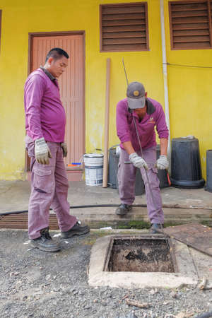 Muadzam Shah, Malaysia - January 3rd, 2019 : The worker clears the clogged sewer drain using a special tool to remove the dirt attached to the channel