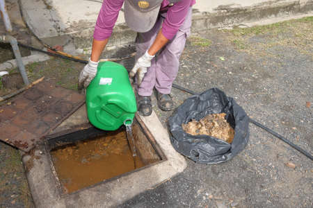 Muadzam Shah, Malaysia-  January 3rd , 2018 : The worker removing mud, dirt, soil, garbage from the drainage pipe  using scoop