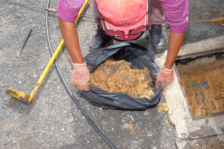 The worker removing mud, dirt, soil, garbage from the drainage pipe  using scoop Banque d'images