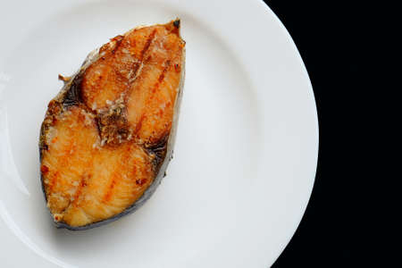 A grilled mackerel fish on white plate  over black background