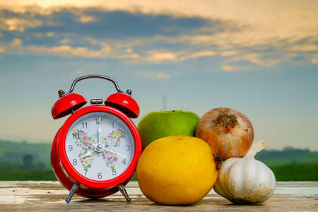 Garlic, onion, lemon, alarm clock   and green apple on old wooden with blurred background , healthy nutrition, strengthening immunity and treatment of flu