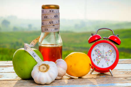 Fresh organic honey in glass jar , measuring tape, green epal , lemon ,garlic and alarm clock  on old wooden with blurred background , healthy nutrition, strengthening immunity, diet and treatment of flu