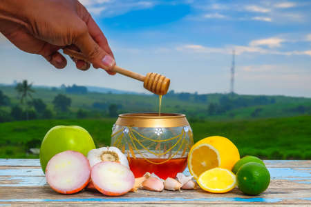 Honey dripping from a wooden honey dipper in a jar. Fresh honey in glass jar , garlic, onion, lime,  lemon and green apple on old wooden with blurred background . Healthy nutrition and strengthening immunity