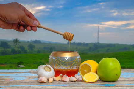 Honey dripping from a wooden honey dipper in a jar. Fresh honey in glass jar , garlic, lemon and green apple on old wooden with blurred background , healthy nutrition, strengthening immunity and treatment of flu Фото со стока