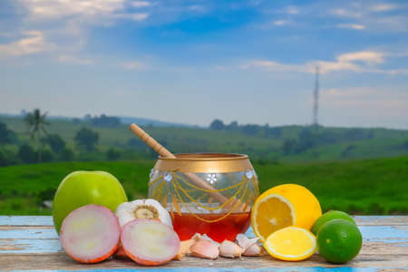 Fresh honey in glass jar , garlic, onion, lime,  lemon and green apple on old wooden with blurred background . Healthy nutrition and strengthening immunity Stock Photo