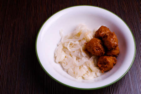 Kuey teow and meatballs  in a white bowl on the table