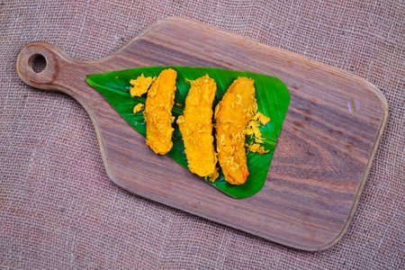 Fried slices of the ripe BANANA also called Pisang Goreng ON BANANA LEAF OVER THE WOODEN CUTTING BOARD