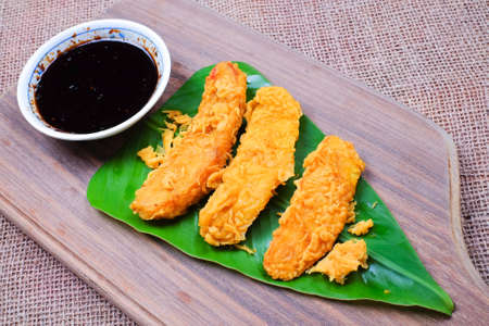 Fried slices of the ripe BANANA also called Pisang Goreng, which are eaten as snack or used to accompany dishes in Malaysia with soy  souce on the table.