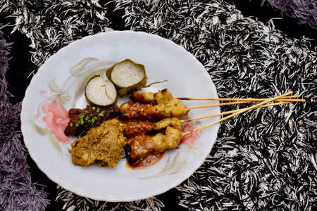 Chicken satay, Lemang and Rendang  on the white plate. Traditional Malay food, Eid Fitr dish. Malaysian cuisine.