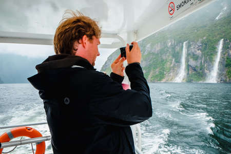 Mildford Sound, New Zealand – December 17th, 2017 : Tourist photographing on a Sightseeing Tour Boat in Milford Sound.