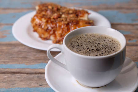 A cup of coffee and Popia- Malaysian traditional dessert, filed with bean sprouts, nuts and chili sauce. Stock Photo