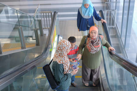 KUALA LUMPUR, MALAYSIA - December 31st ,  2017: Asian Malay mother with  son and daughters taking escalator at MRT Station . MRT is Mass Rapid Transit Corporation Sdn Bhd, in Kuala Lumpur, Malaysia.