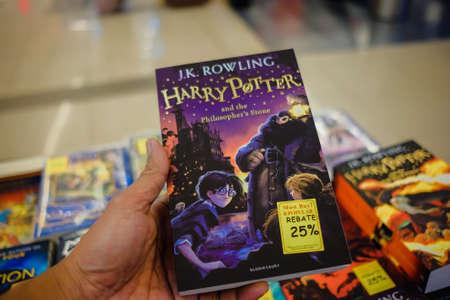 KUALA LUMPUR, MALAISIE - 31 décembre 2017 : Homme tenant le livre « Harry Potter » exposé à la librairie populaire, Kuala Lumpur. Popular est l'un des plus grands libraires de détail en Malaisie.