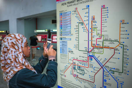 KUALA LUMPUR, MALAYSIA - December 31st, 2017:  Malay young girl taking photo of the Mass Rapid Transit route map signage in KLCC MRT train station in Kuala Lumpur.