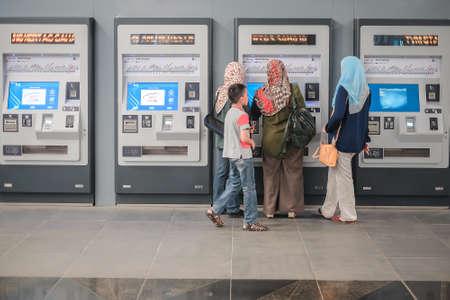 KUALA LUMPUR, MALEISI - 31 december 2017: Passagier die een kaartje koopt bij automaten op Bukit Dukung Mass Rapid Transit (MRT)-stations.