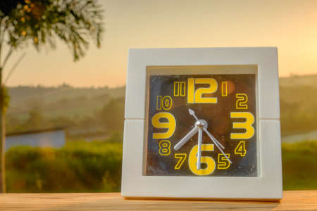 Good morning concept.  White alarm clock on wooden table over sunrise at grazing field background. Copy space Stock Photo