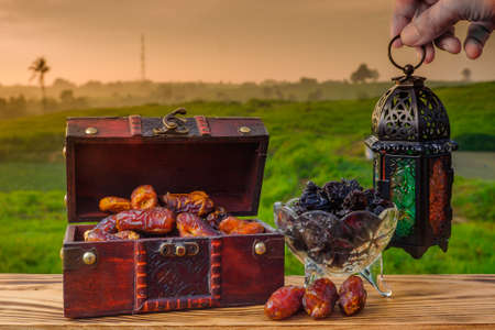 Lighting Ramadan Lantern , black raisin  and  dates    on old wood with a beautiful sunrise as background. Holy month of Ramadan concept. Imagens